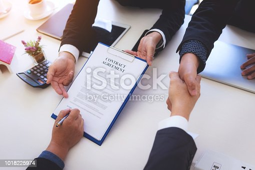 638881988istockphoto closeup hand of business man signing contract document and handshaking after finished meeting. 1018225974