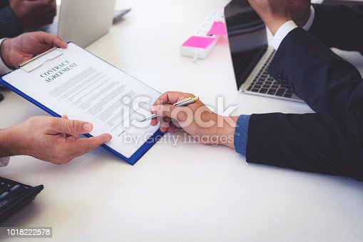 1008974324 istock photo closeup hand of business man signing contract document 1018222578