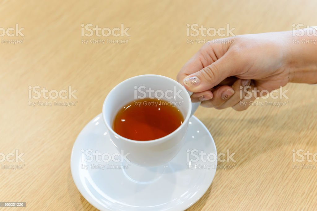 Closeup hand of female holding a cup of hot tea in the meeting room royalty-free stock photo