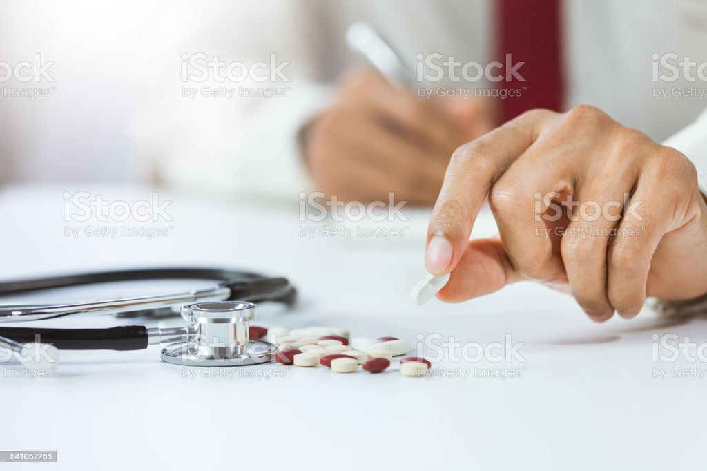 Close-up hand of male doctor holding and showing pills in office stock photo