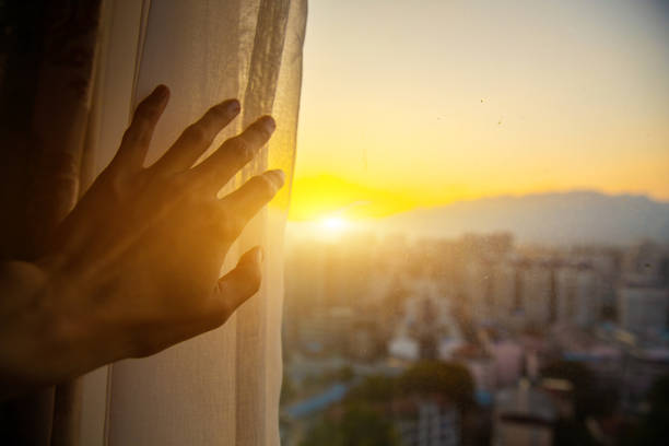 Close-up hand open window curtain in the morning stock photo