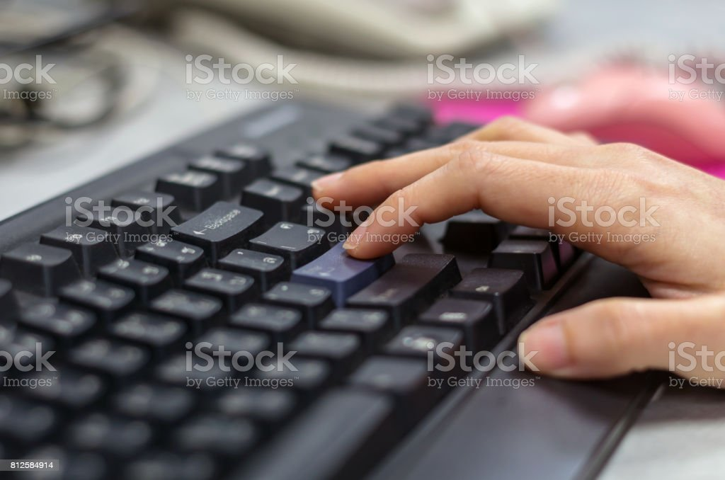 closeup hand press the enter button of keyboard on working table with mouse blurred background stock photo