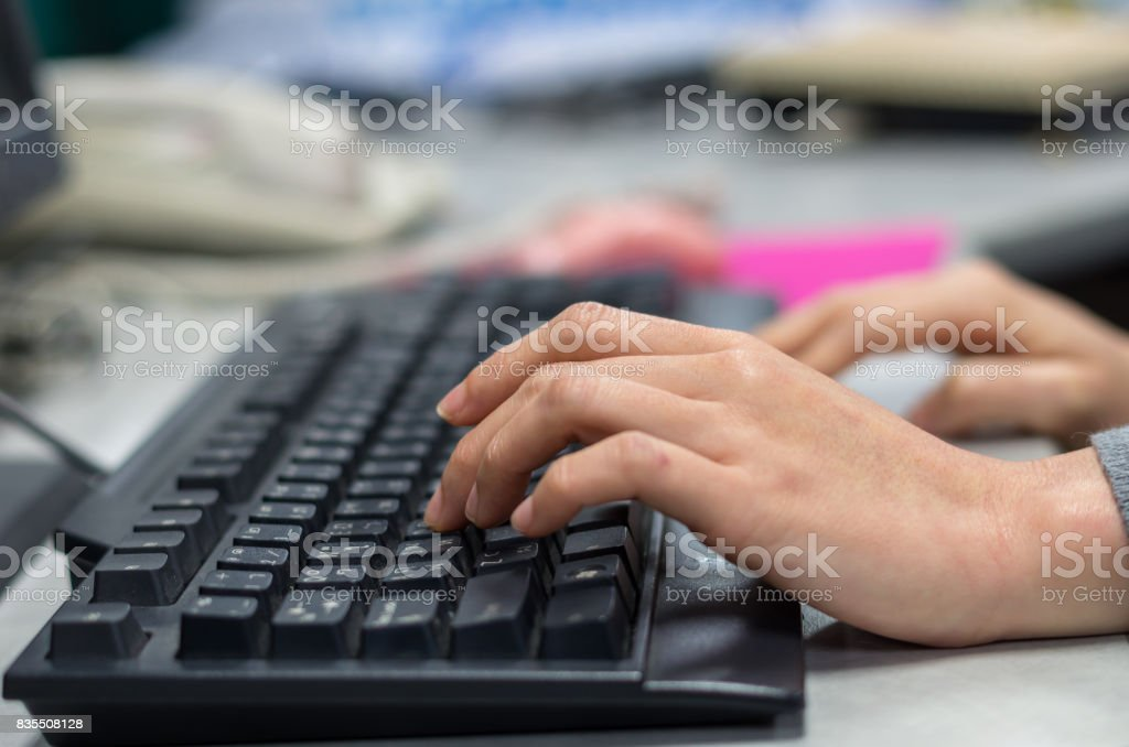 closeup hand press the old keyboard on working table with mouse blurred background stock photo