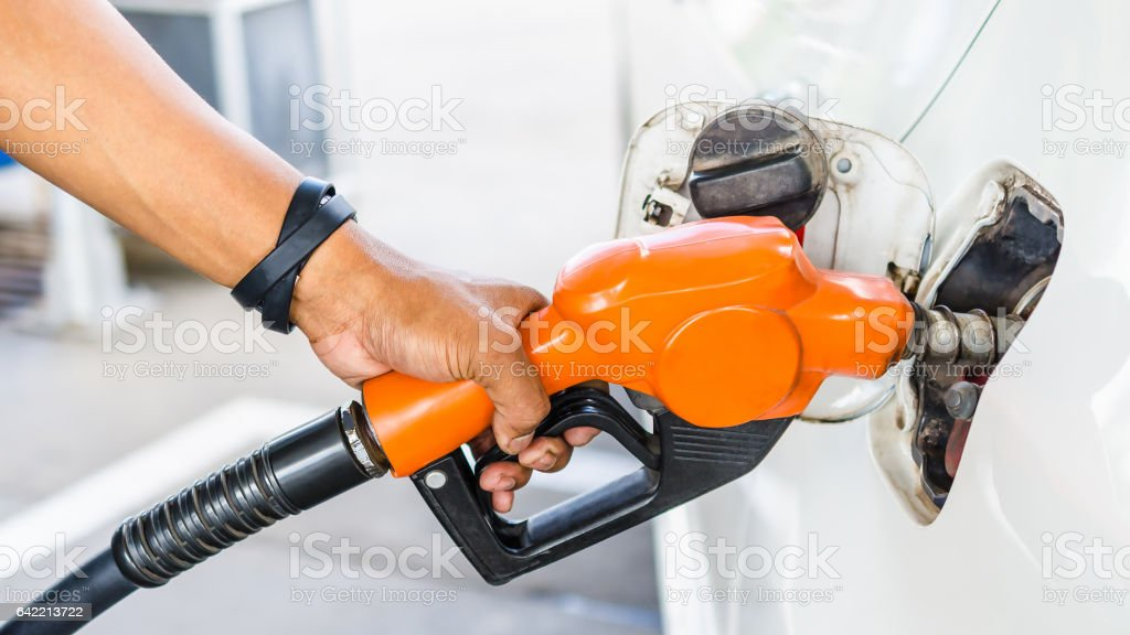 Closeup hand pumping Fuel nozzle gasoline fuel in white car at gas station stock photo