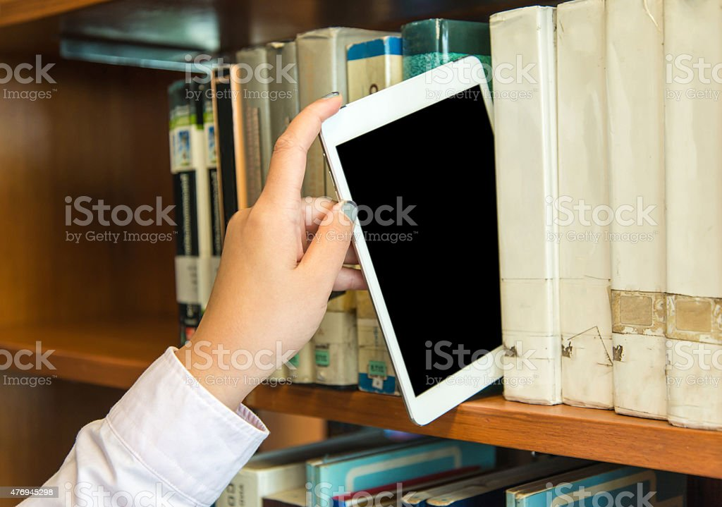 Closeup hand putting a tablet pc in the library stock photo