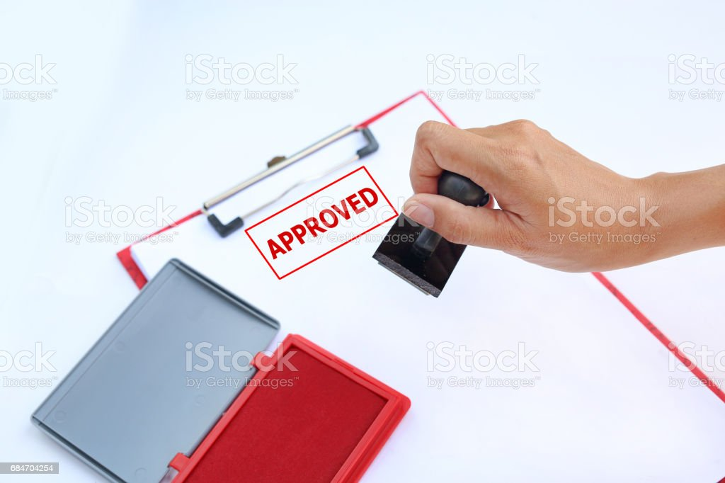 Close-up hand Stamping APPROVED on paper sheet with red Ink pad(box) against white background. stock photo