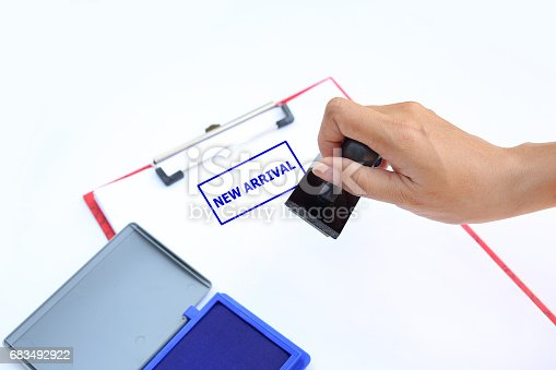 istock Close-up hand Stamping NEW ARRIVAL on paper sheet. 683492922