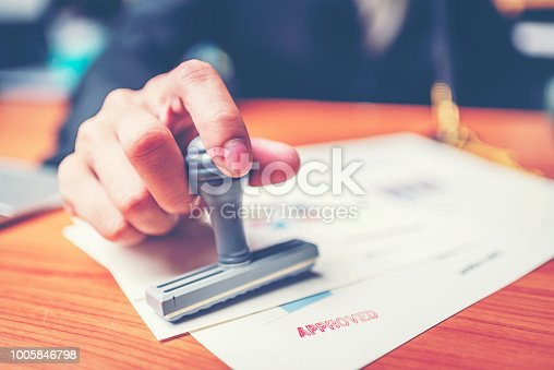 istock Close-up hand stamping of businessman for signing approval on documents , business concept 1005846798