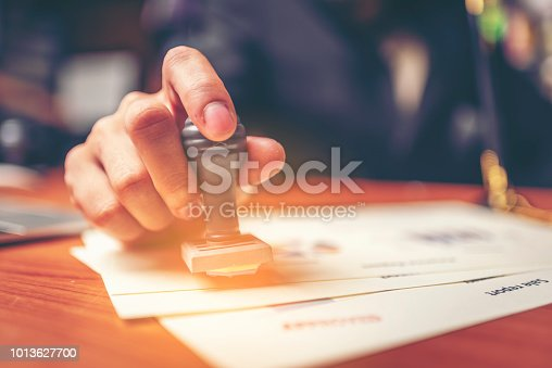 istock Close-up hand stamping of businessman for signing approval on documents , business concept 1013627700