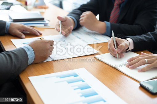 istock Closeup hand team business analysts make decisions about the US economy that affect future operations of the company.concept 1194497340