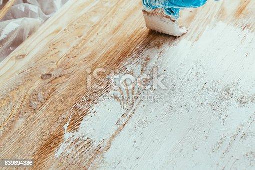 istock closeup hand use brush paint white on wood surface 639694336