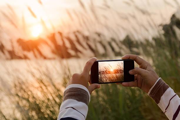 nahaufnahme der hand die landschaft foto mit telefon - schönen abend bilder stock-fotos und bilder