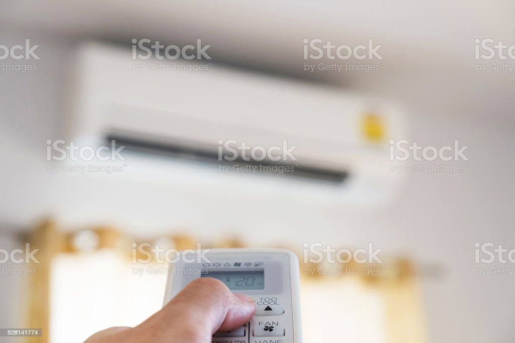 Close-up hand using remote control of air condition, selective focus stock photo