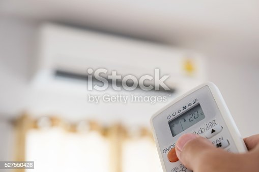 istock Close-up hand using remote control of air condition, selective focus 527550426