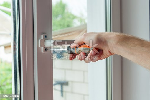 966792200 istock photo Close-up, hand with a screwdriver tightens the fixing screw of the window limiter. 859438380