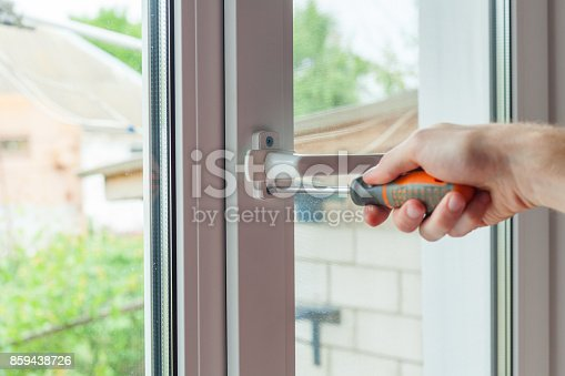 966792200 istock photo Close-up, hand with a screwdriver tightens the fixing screw of the window limiter. 859438726