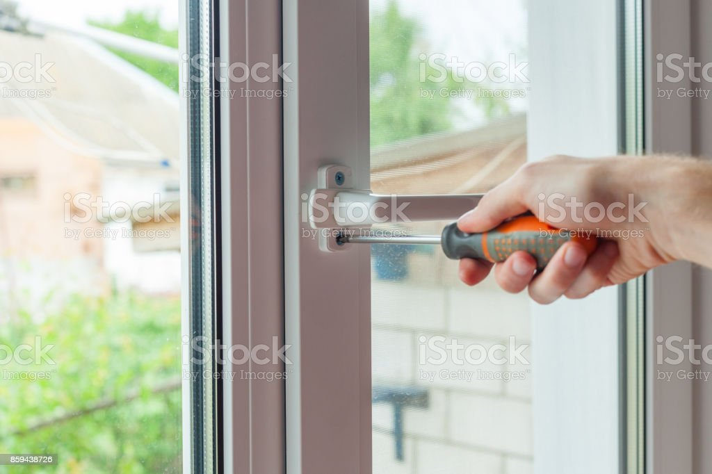 Close-up, hand with a screwdriver tightens the fixing screw of the window limiter. stock photo