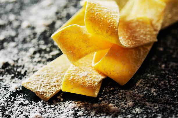 close-up handmade pasta diagonal on a dark with flour background – Foto