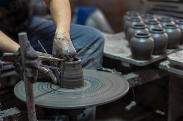 närbild händerna på en krukmakare, skapa ett lerkärl burk på traditionella maskinen, svagt ljus - balpress bildbanksfoton och bilder