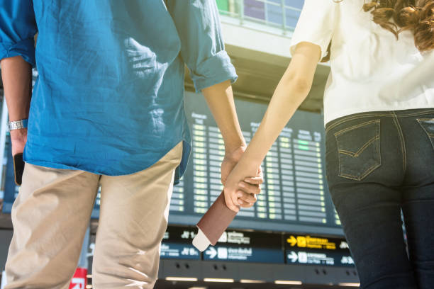 closeup hands of asian couple holding the passport over the photo bluured of flight information on the bug board in modern an airport, travel and transportation with technology concept. - aids healthcare foundation foto e immagini stock