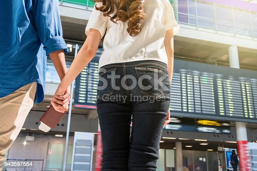 842907838 istock photo Closeup hands of asian couple holding the passport over the photo bluured of flight information on the bug board in moddern an airport, travel and transportation with technology concept. 943597554