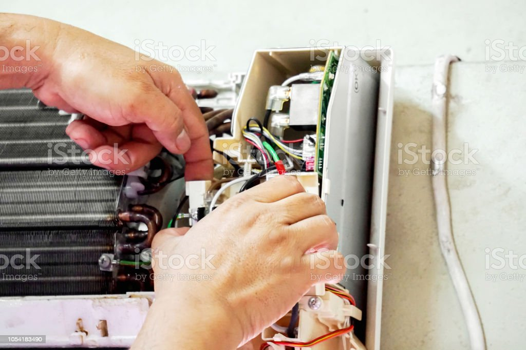 Closeup hands of electric repair technician fix an electronic board of home's air conditioner after washing in the bedroom. stock photo