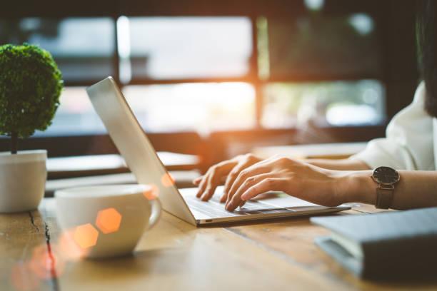 closeup mãos de mulher freelancer trabalhando usando digital portátil computador e beber café café da manhã na mesa de trabalho na loja de café da manhã. - laptop - fotografias e filmes do acervo