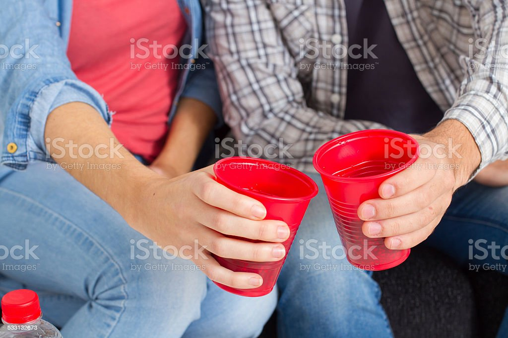 Closeup hands of friends toasting with red plastic cups stock photo