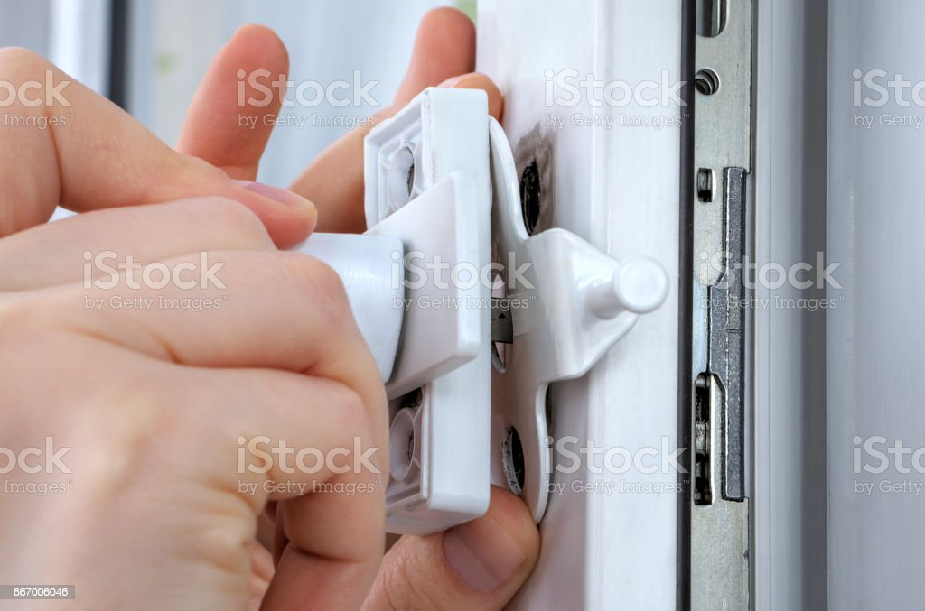 Close-up hands of locksmith  installing window limiter on plastic frame. stock photo