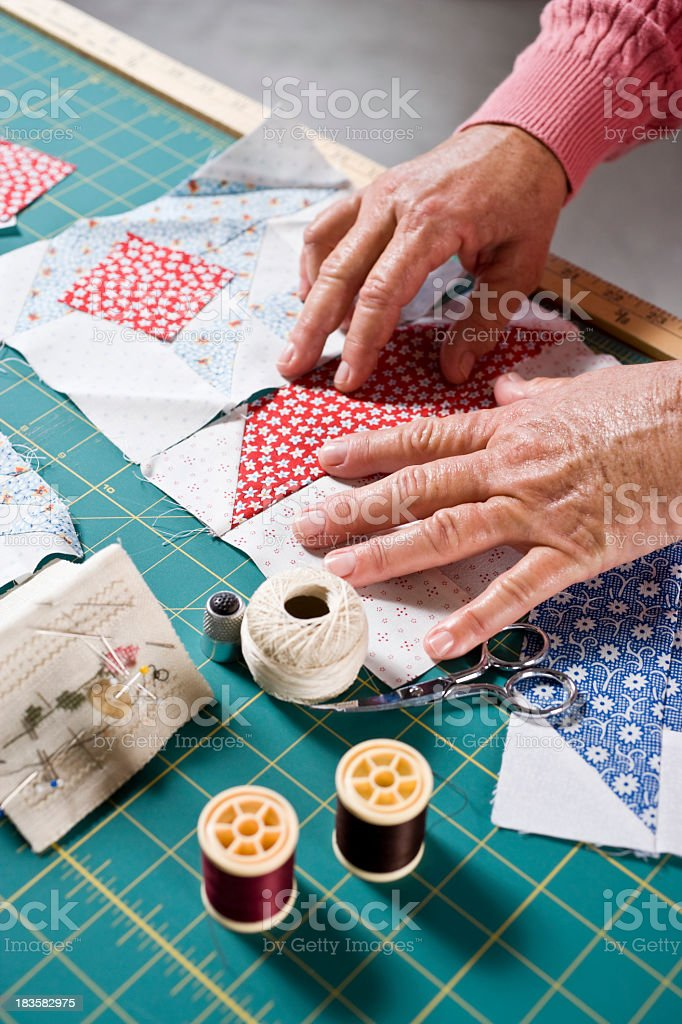 Close-up hands of senior woman sewing quilt stock photo