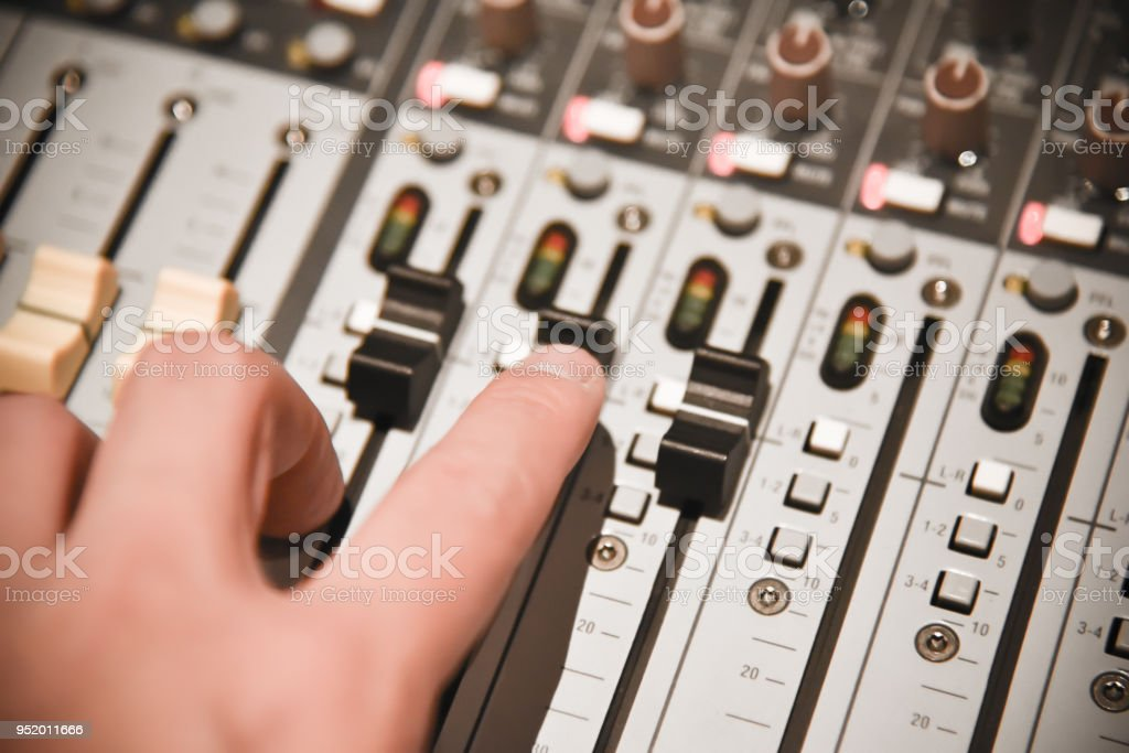 close-up hands of sound engineer adjusting audio mixer controller for...