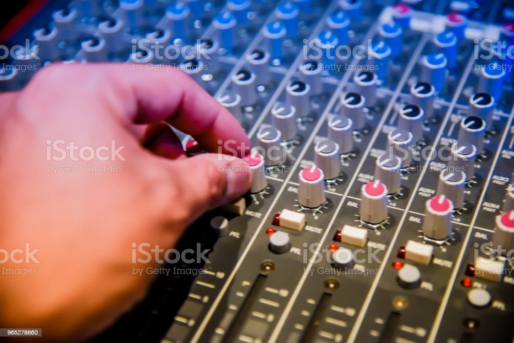 close-up hands of sound engineer adjusting audio mixer controller for live music and studio equipment. This is a quality audio system for professionals. vintage tone & effect light in control room. zbiór zdjęć royalty-free