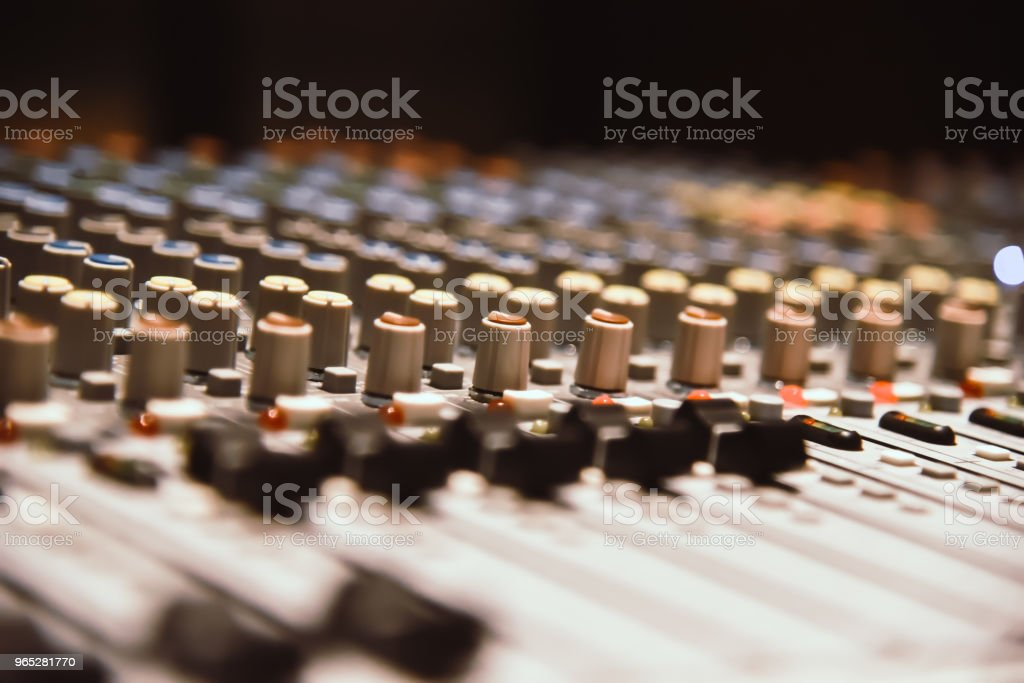 close-up hands of sound engineer adjusting audio mixer controller for live music and studio equipment. This is a quality audio system for professionals. vintage tone & effect light in control room. royalty-free stock photo