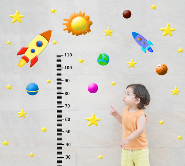 Closeup happy asian kid stand and point to scale of measure height with cute cartoon at the marble stone wall textured background in growth of kid concept stock photo