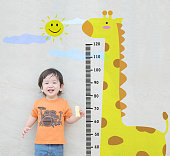 istock Closeup happy asian kid stand for measure height with cute cartoon at the marble stone wall textured background 909842566