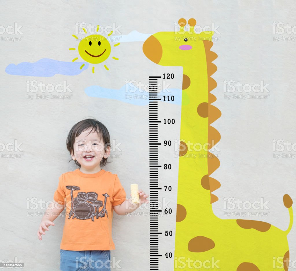 Closeup happy asian kid stand for measure height with cute cartoon at the marble stone wall textured background stock photo