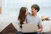 クローズ アップ ハッピー アジア恋人やカップルの話とラップトップを使用して技術ベッド ルームのベッドの上現代家で若い女性の彼氏、恋人、ライフ スタイル概念の鼻を指しているとき�