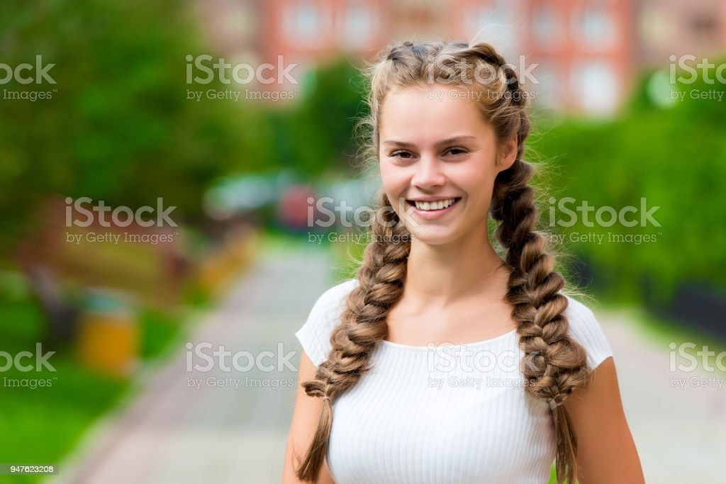 closeup happy st 20- year-old woman in a white T-shirt with two braids in the park stock photo