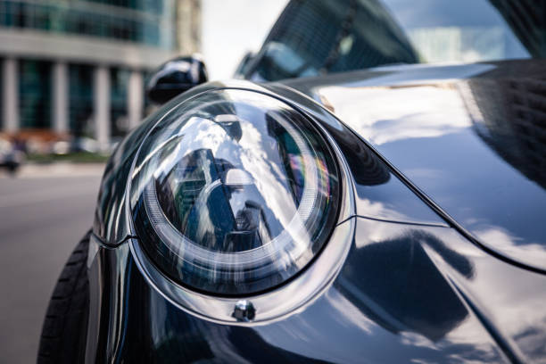 Closeup headlights of new shiny luxury dark blue sports car Porsche 911 parked on street, front bottom view, sky reflection on bonnet, bumper Russia Moscow 2019-06-17 Closeup headlights of new shiny luxury dark blue sports car Porsche 911 parked on the street, front bottom view, sky reflection on bonnet, bumper porsche stock pictures, royalty-free photos & images