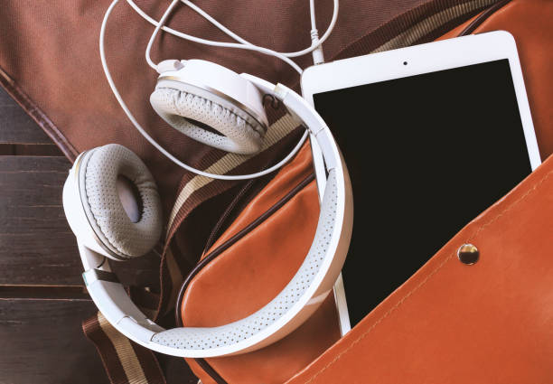 closeup headphones and tablet computer in bag on wooden table with soft-focus in the background. film colors tone – zdjęcie