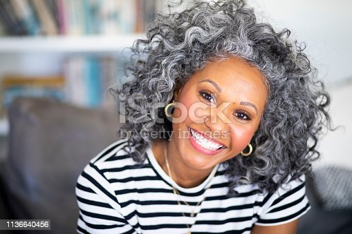 A beautiful black woman with white curly hair  smiles for a headshot