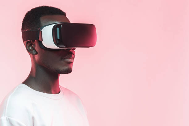 closeup headshot of african man pictured on pink background with vr headset on - ritratto 360 gradi foto e immagini stock