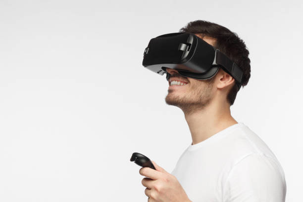 closeup headshot of young handsome european man pictured isolated on gray background wearing virtual reality headset and smiling while pressing button on remote control he is holding in hand - man joystick imagens e fotografias de stock