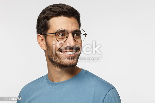 istock Closeup headshot of young man in round eyeglasses isolated on gray background, smiling happily, looking right, feeling positive, relaxed and joyful 1041103738