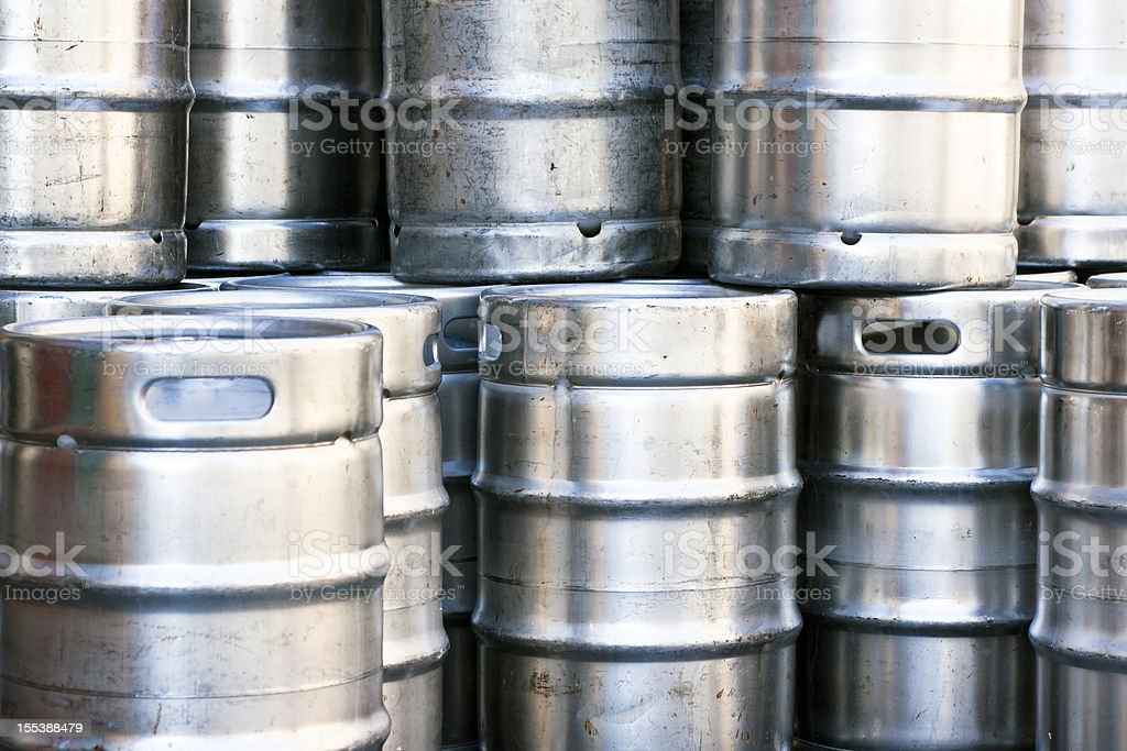 Closeup heap of shiny stainless steel beer kegs stock photo