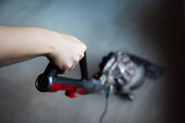 closeup, high angle, above, looking down view of hand holding handle of vacuum cleaner cleaning room carpet floor - poprawna postawa zdjęcia i obrazy z banku zdjęć