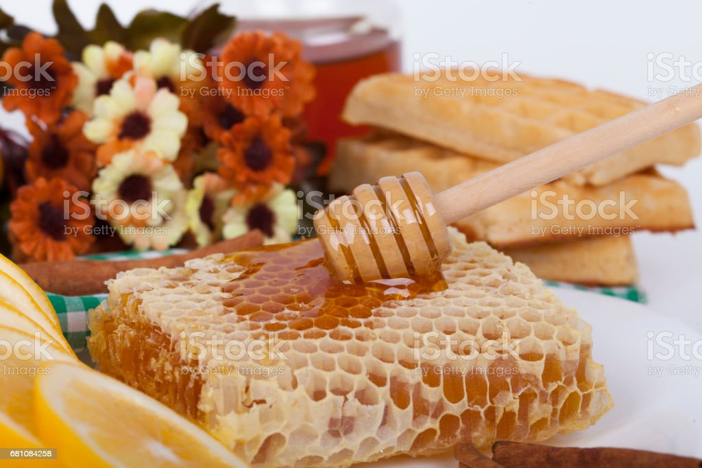 Close-up honeycomb topped with honey and dipper on a table royalty-free stock photo