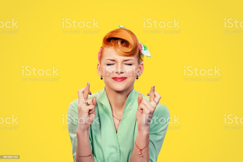 Closeup  hopeful beautiful young woman pin up style retro crossing her fingers eyes closed hoping asking best isolated yellow background. Human face expression emotions feeling attitude reaction - foto de stock