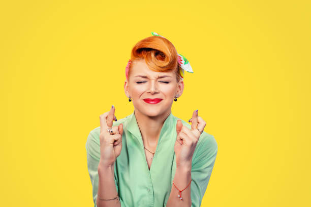Closeup  hopeful beautiful young woman pin up style retro crossing her fingers eyes closed hoping asking best isolated yellow background. Human face expression emotions feeling attitude reaction stock photo
