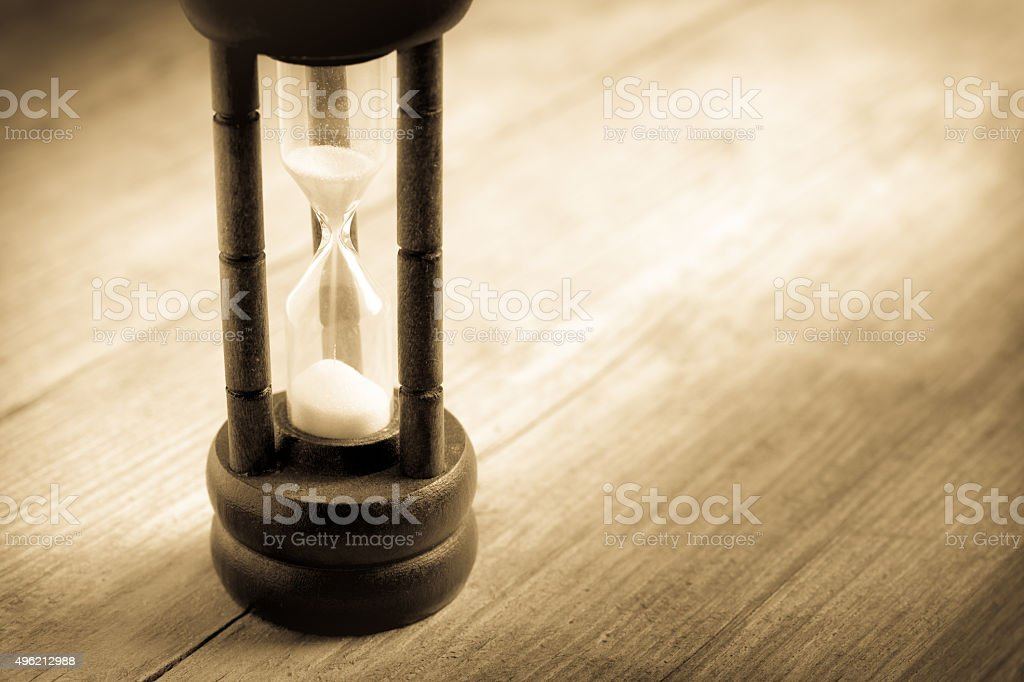 Close-up Hourglass on wood background , antique tone stock photo